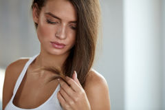 Beautiful Woman With Split Ended Hair. Hair Care Concept. Health And Beauty. Portrait Of Beautiful Sad Young Woman With Long Hair In Hand. Closeup Of Unhappy Royalty Free Stock Photo