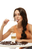 Beautiful woman with spoon in her mouth sitting at Royalty Free Stock Photography