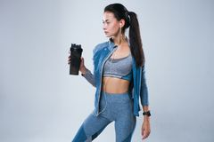 Beautiful woman in sport wear posed with bottle of water and listening to music in earphones. While standing isolated over gray background Stock Photos