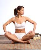 Beautiful woman in sports bra sitting on mat stock photo