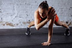 Beautiful woman in sportswear doing plank while trainnig at cross fit gym. Young beautiful woman in sportswear doing one handed plank while trainnig at cross fit royalty free stock image