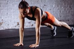 Beautiful woman in sportswear doing plank while trainnig at cross fit gym. Young beautiful woman in sportswear doing plank while trainnig at cross fit gym royalty free stock photo