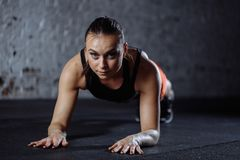 Beautiful woman in sportswear doing plank while trainnig at cross fit gym stock photos