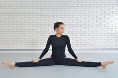 Beautiful woman in sportswear exercising at fitness studio, performing twine sitting on the floor. Beautiful woman in sportswear exercising at fitness studio royalty free stock photography