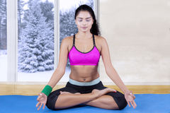 Beautiful woman with sportswear meditating at home Stock Image