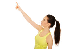 Beautiful woman in sportswear pointing up. Stock Photography