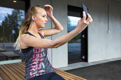 Beautiful Woman In Sportswear Taking Selfie While Sitting On Ben Stock Photography