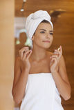 Beautiful woman spraying herself perfume Stock Photo