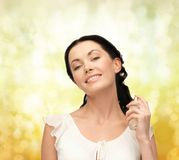 Beautiful woman spraying pefrume on her neck Royalty Free Stock Photo