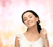 Beautiful woman spraying pefrume on her neck Royalty Free Stock Image