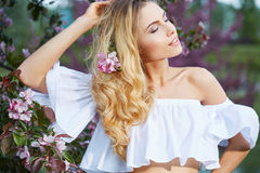 Beautiful woman in spring blossom trees. Royalty Free Stock Photo