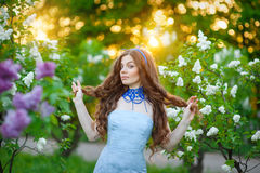 Beautiful woman in the spring garden with lilac wreath cats Royalty Free Stock Photo