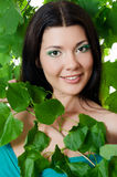 Beautiful woman with spring green leaves Stock Images