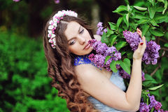Beautiful woman in a spring park smelling the lilacs Stock Photo