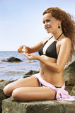 Beautiful woman squeezes out a cream for sunburns Royalty Free Stock Images