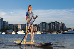 Beautiful woman on Stand Up Paddle Board. SUP. Young pretty woman on Stand Up Paddle Board. SUP. Shape of a city on background Stock Image