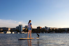 Beautiful woman on Stand Up Paddle Board. SUP. Young woman on Stand Up Paddle Board. SUP. Shape of a city on background Royalty Free Stock Image