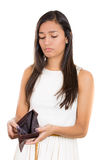 beautiful woman standing against white background with an empty wallet, surprised and sad. Stock Photo