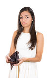 Beautiful woman standing against white background with an empty wallet, surprised and sad. Stock Image