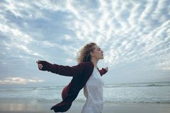 Beautiful woman standing arm stretched at beach. Side view of beautiful young Caucasian woman with curly hair standing arm stretched at beach. She is relaxed stock photography