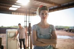 Woman standing with arms crossed at petrol pump station Royalty Free Stock Images