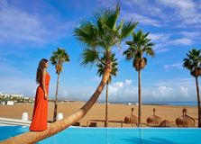 Beautiful woman standing on bent palm tree. Trunk at infinity pool long red dress Royalty Free Stock Photos