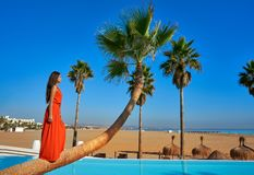 Beautiful woman standing on bent palm tree. Trunk at infinity pool long red dress Stock Photography