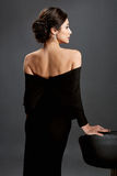 Beautiful woman standing in a black dress over gray background Royalty Free Stock Images