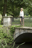 Beautiful woman standing on the bridge in the Park. Stock Photo
