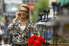Beautiful  woman standing on a busy street talking on a cell phone. Royalty Free Stock Images