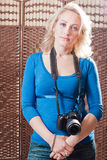 Beautiful woman standing with camera around her neck Stock Photo