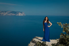 Beautiful woman standing on a cliff over blue sky. Brunette girl Royalty Free Stock Image