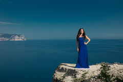 Beautiful woman standing on a cliff over blue sky. Brunette girl Stock Photos