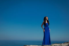 Beautiful woman standing on a cliff over blue sky. Brunette girl Royalty Free Stock Images