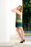 Beautiful woman is standing at the column. Royalty Free Stock Photos