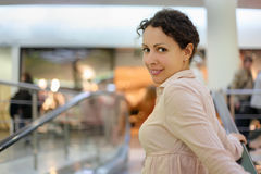 Beautiful woman standing on escalator Royalty Free Stock Photos