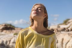 Beautiful woman standing with eyes closed at beach. On a sunny day royalty free stock photography