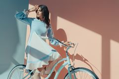 Beautiful woman standing in fashionable turquoise dress with long sleeves and sitting on bicycle and looking. For someone stock images