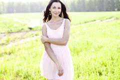 Beautiful woman standing in a field pink dress, fashion style, the concept of portrait outdoor Royalty Free Stock Photography