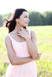 Beautiful woman standing in a field pink dress, fashion style, the concept of portrait outdoor Stock Photography