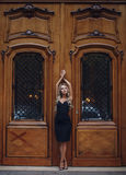 Beautiful woman standing in grace pose near vintage doors. Beautiful blonde woman in black dress standing in grace pose near the vintage wooden doors. Chic and Royalty Free Stock Photo