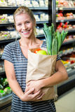 Beautiful woman standing with grocery bag Stock Photo