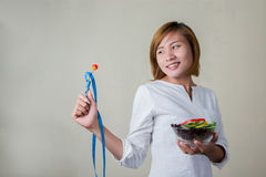 Beautiful woman standing holding bowl of salad looking at fork d Royalty Free Stock Image