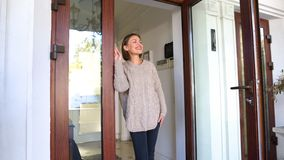 Beautiful woman standing by house and smiling, waiting for husband from work royalty free stock image