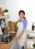 Beautiful woman standing in kitchen with apron Royalty Free Stock Image