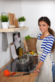 Beautiful woman standing in kitchen with apron Royalty Free Stock Photo