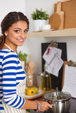 Beautiful woman standing in kitchen with apron Stock Photography