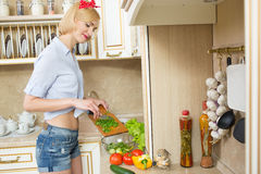 Beautiful woman standing in kitchen royalty free stock image