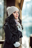 Beautiful woman is standing and looking afar. Outside photo shoot. Winter. A girl is in warm clothes and with hat on head. Nice make up and curly hairs Stock Images