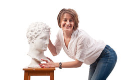 Beautiful woman standing near antique man statue and touches his Stock Image